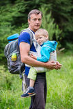 Caucasian man carrying his son in sling Stock Photo