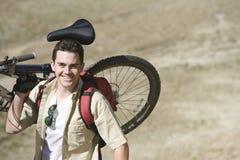 Caucasian Man Carrying Mountain Bike Stock Images
