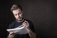 Caucasian man in casual t-shirt reading documents Royalty Free Stock Image