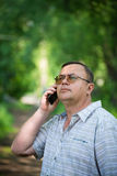 Caucasian man with cell phone. In nature Stock Photos