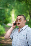 Caucasian man with cell phone. In nature Stock Images