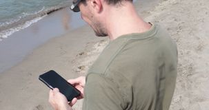 Man checking messages on the beach