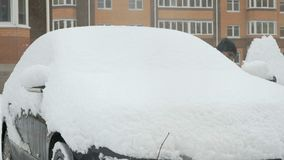 Man cleaning car from snow. Caucasian man is cleaning black car from snow during snowfall in the yard stock video