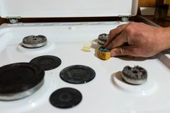 Caucasian man cleaning the dirty gas stove royalty free stock photography