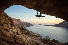 Caucasian man climbing challenging route in cave at sunset. Caucasian man climbing challenging route in cave, against beautiful evening view stock image