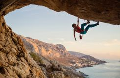 Caucasian man climbing challenging route going along ceiling in cave at sunset. Against beautiful evening view stock photography