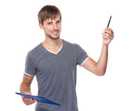 Caucasian man with clipboard and pen up Stock Images