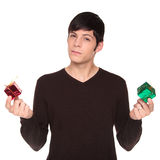 Caucasian man comparing green present to red Royalty Free Stock Images