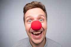 Caucasian man with crazy look wearing a clown nose. Concept of happy birthday party, being in good mood stock images