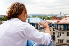 Caucasian man with a cup coffee outdoors. Caucasian man sitting with a cup coffee outdoors Royalty Free Stock Photo