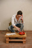 A caucasian man is dialing a phone number. A caucasian man in casual clothes is dialing a phone number at his table Stock Images