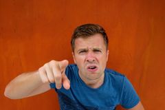Caucasian man dissatisfied frowns. Poking his finger ahead. He is unhappy and angry Royalty Free Stock Image