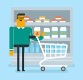 Caucasian man doing shopping in the supermarket. Caucasian white man walking with basket on aisle with dairy products in the supermarket. Man holding an empty Royalty Free Stock Image