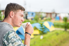 Caucasian man drinking coffee. In camping area Royalty Free Stock Photo