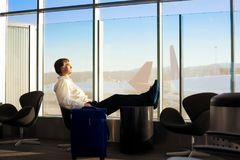 Caucasian businessman sleeping in airport terminal, planes in ba. Caucasian man in early fifties, side profile, sleeping with legs up in airport terminal royalty free stock photos