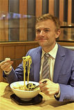 Caucasian man eating noodles in restaurant Royalty Free Stock Images