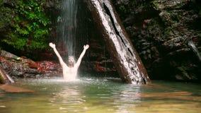 caucasian man enjoying in waterfall under water stock video