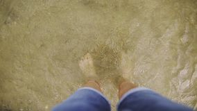 Caucasian man enters the sea water. Close-up of the male legs walking along the golden sand into the water, high up view. Caucasian man enters the sea water stock video footage