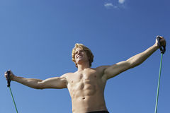 Caucasian Man Exercising Against Blue Sky Stock Photo