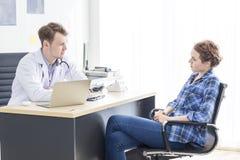 Caucasian man för medicinska professionell som uppmuntrar och talar med spänningspatienten för ung kvinna arkivbilder