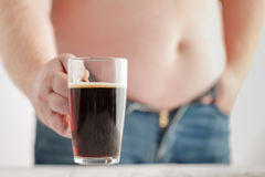 Caucasian man with Fat Beer Belly, holding a glass of dark ale. Stock Photo
