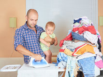 Caucasian man father and son in his hands, ironed clothes in the Royalty Free Stock Photo