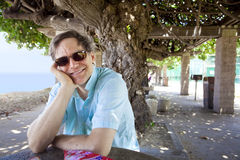 Caucasian man in forties relaxing under shaded tree canopy Royalty Free Stock Images