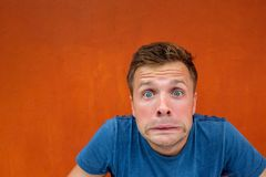 Caucasian man with funny face on red background. Concept of unexpected news Royalty Free Stock Images