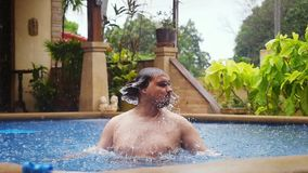 Caucasian man gets rained enjoyes while swimming in pool on vacation in slow motion. 1920x1080. Hd stock video