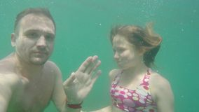 Caucasian man and girl dive into sea and waving their hands in the camera under the water. White man and girl dive into sea and waving their hands in the camera stock video footage