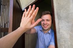 Caucasian man giving five to his neighbor. Make an agreement or welcome a guest stock photos