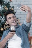 The caucasian man with glass of red wine is taking a selfie with royalty free stock photo