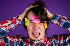 Caucasian man grabs his head and cries, close-up portrait. A man is shocked by his obligations and routine. Stickers on. Face on a purple background Stock Photos