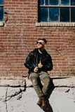 Caucasian man Guy Walking för ungt attraktivt modernt mode och att sitta, le och skratta utanför stads- gammal övergiven tegelste arkivbild