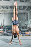 Caucasian man gymnastic acrobatics equilibrium posture at gym background. The caucasian man gymnastic acrobatics equilibrium posture at gym background Stock Image
