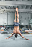 Caucasian man gymnastic acrobatics equilibrium posture at gym background. The caucasian man gymnastic acrobatics equilibrium posture at gym background Stock Images