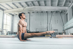 Caucasian man gymnastic acrobatics equilibrium posture at gym background. The caucasian man gymnastic acrobatics equilibrium posture at gym background Royalty Free Stock Photography