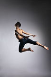 Caucasian man gymnastic leap posture on grey. Background Royalty Free Stock Photos