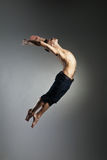Caucasian man gymnastic leap posture on grey. Background Stock Photography