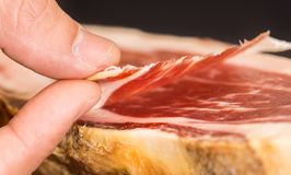 Caucasian man hand takes slices from Serrano ham Stock Photos