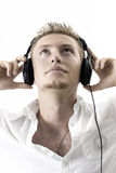 Caucasian man with headphones. A caucasian man listening to headphones music with a white background. His head is facing upwards and both his hands are Stock Photo