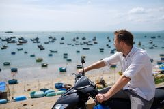 Caucasian man without helmet sit on motorbike. On background is ocean with famous small vietnam boats. Travel around asia on bike Stock Image