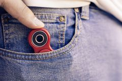 Caucasian man hides his red finger fidget spinner at jeans pocket. Popular spinner gadget in 2017.  royalty free stock images