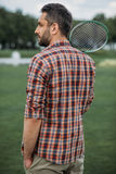 Caucasian man holding badminton racquet and standing on green field Stock Photo