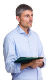 Caucasian man holding clipboard and looking aside Royalty Free Stock Images