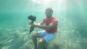 A caucasian man holding a DSLR camera with tripod filming underwater. Waterproof camera, shooting underwater stock footage