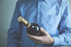 Caucasian man holds a bottle of wine. stock photos