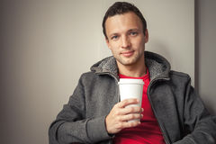 Caucasian man in hoodie sitting in cafe with paper cup Royalty Free Stock Photo