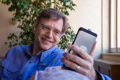 Caucasian man, i att le för forties som ser mobiltelefonen royaltyfri fotografi