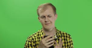 Caucasian man i gult bläddra för skjorta som smsar på smartphonen i hans händer lager videofilmer